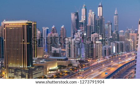Beautiful aerial top view day to night transition  of Dubai Marina and JLT skyscrapers in Dubai, UAE. Modern towers and traffic on sheikh zayed road with metro line and tram station