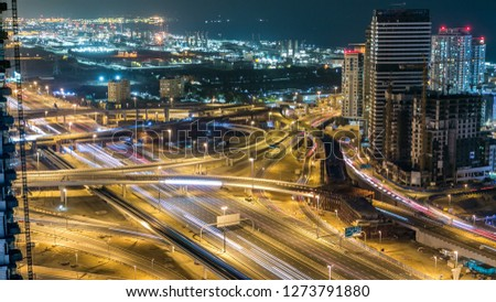 Beautiful aerial top view of highway intersection at night  near Dubai Marina skyscrapers in Dubai, UAE. Illuminated modern towers with blinking lights and traffic on the road and metro line.