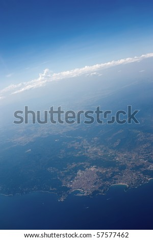 Beautiful aerial view from the plane on spanish coastline with clouds and skyline in the back.