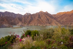 BEAUTIFUL AERIAL VIEW OF  BOATS, KAYAKS IN THE RAFIS WATER DAM  AT SUNSET TIME IN THE MOUNTAINS ENCLAVE REGION OF KHOR FAKKAN, SHARJAH UNITED ARAB EMIRATES