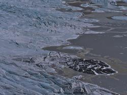 Beautiful aerial view of break-off edge of Skaftafellsjökull glacier, part of Vatnajökull ice cap, in Skaftafell national park in southern Iceland in winter season with rock and floating icebergs.