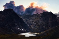 Beautiful Aerial View of Dramatic Mountains and Scenic Alpine Lake during Fall in Canadian Nature. Dramatic Colorful Sunset Artistic Render. Taken in Tombstone Territorial Park, Yukon, Canada.