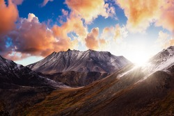 Beautiful Aerial View of Dramatic Mountains and Scenic Alpine Lake during Fall in Canadian Nature. Dramatic Colorful Sunset Artistic Render. Tombstone Territorial Park, Yukon, Canada.