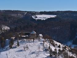 Beautiful aerial view of historic castle ruin Niedergundelfingen located on the top of a hill in Große Lauter valley in Gundelfingen, Münsingen, Germany in Swabian Alb in winter season with snow.