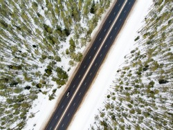 Beautiful aerial view of snow covered fields with a two-lane road among trees. Rime ice and hoar frost covering trees. Scenic winter landscape near Vilnius, Lithuania.