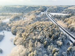 Beautiful aerial view of snow covered pine forests and a road winding among trees. Rime ice and hoar frost covering trees. Scenic winter landscape near Vilnius, Lithuania.