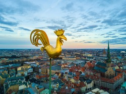 Beautiful aerial view of the city from above with a golden cock in the middle. Sunset time.