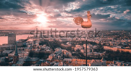 Photo of Beautiful aerial view of the city from above with a golden cock in the middle. Sunset time.