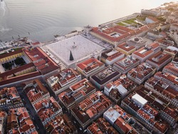 Beautiful aerial view of the Lisbon main square in Portugal. Drone view of Praca do Comercio near the Tagus river with the April 25th bridge in the background at sunset.