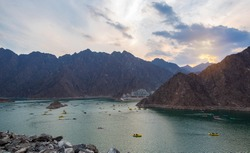 BEAUTIFUL AERIAL VIEW OF THE PADDLE BOATS, KAYAKS IN THE HATTA WATER DAM ON A CLOUDY DAY AT SUNSET TIME IN THE MOUNTAINS ENCLAVE REGION OF DUBAI, UNITED ARAB EMIRATES.