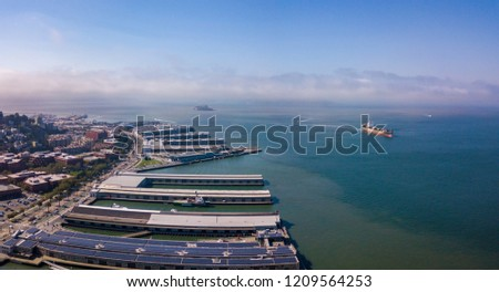 Beautiful aerial view of the San Francisco docks with many piers including pier 39 and Alcatraz prison in the middle of the bay. #1209564253