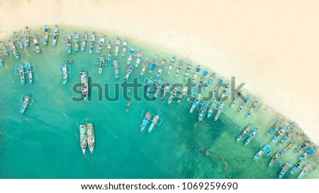 Beautiful aerial view of traditional fisherman boats in a row on the Ujung Genteng beach with turquoise water, Sukabumi, West Java, Indonesia #1069259690