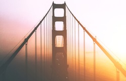 Beautiful Aerial view silhouette of famous San Francisco landmark with name Golden Gate bridge. Scenery bridge tower construction in misty foggy sunset light. Famous California sight in gold sundown