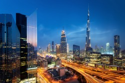 Beautiful aerial view to Dubai downtown city center lights skyline at night, United Arab Emirates. Long exposure light trails effect