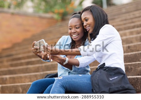 beautiful african american college students using cell phone on campus