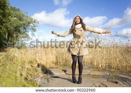 Beautiful african american girl having fun on a beach on autumn - stock photo