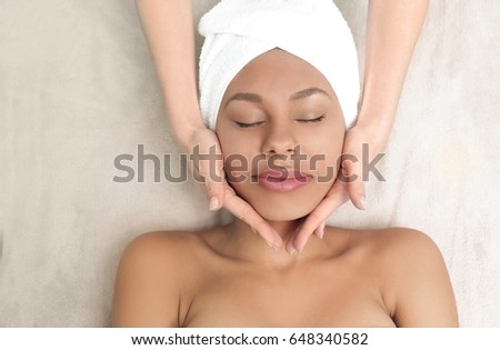 Beautiful African-American girl having massage in spa salon