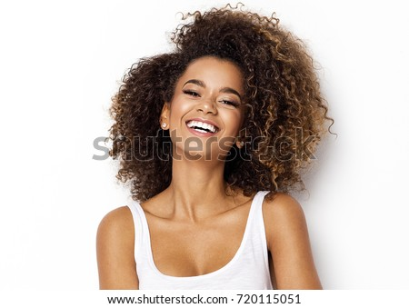 Beautiful african american girl with an afro hairstyle smiling #720115051