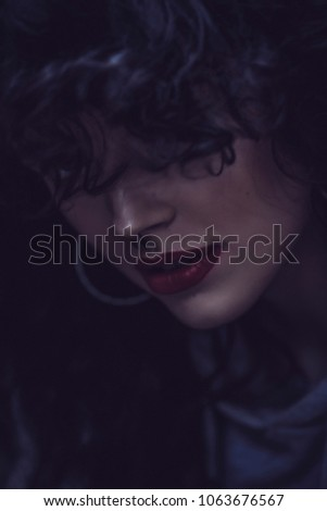 Beautiful african american girl with an afro hairstyle smiling. Close up portrait of a beautiful african american woman face smiling. She looking somewhere. Red lips. Professional photo session