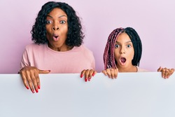 Beautiful african american mother and daughter holding blank empty banner scared and amazed with open mouth for surprise, disbelief face