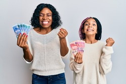 Beautiful african american mother and daughter holding south african rand banknotes screaming proud, celebrating victory and success very excited with raised arm