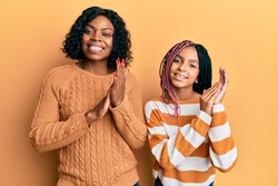 Beautiful african american mother and daughter wearing wool winter sweater clapping and applauding happy and joyful, smiling proud hands together