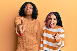 Beautiful african american mother and daughter wearing wool winter sweater pointing displeased and frustrated to the camera, angry and furious with you