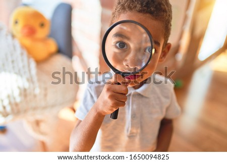 Beautiful african american toddler playing with loupe at kindergarten Stock photo ©