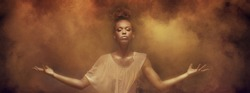 Beautiful african american woman dancer posing over dust. Concept of powerful lady.