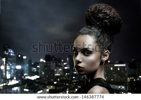 Beautiful African-American woman in front of a big city outline.