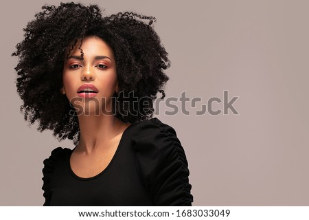 Photo of Beautiful african american woman looking at camera. Portrait of cheerful young woman with afro hairstyle. Beauty girl with curly hair.