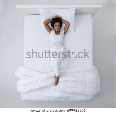 Beautiful african american woman lying in bed and smiling at camera, top view