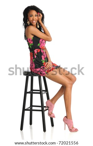 Beautiful African American woman sitting on stool isolated over white background