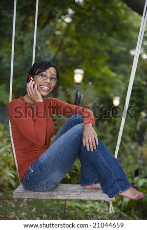 Beautiful African American woman sitting outside on a swing talking on her cell phone