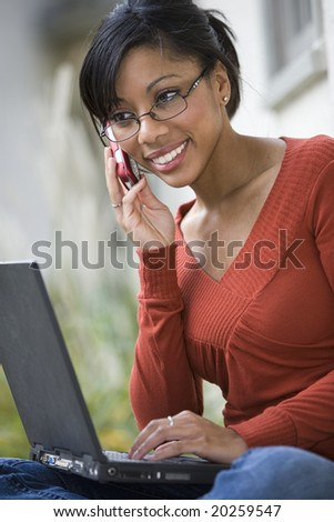 Beautiful African American woman sitting outside using cell phone and laptop