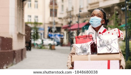 Beautiful African American woman walking in decorated city with many christmas gift boxes after xmas shopping. Portrait of joyful grateful female in mask holds holiday presents. Surprise gifts concept