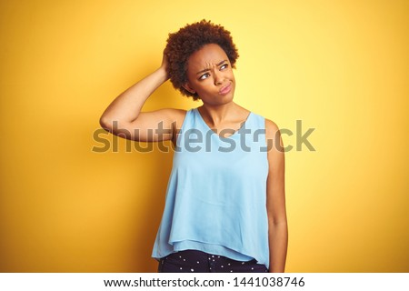 Beautiful african american woman wearing elegant shirt over isolated yellow background confuse and wonder about question. Uncertain with doubt, thinking with hand on head. Pensive concept.