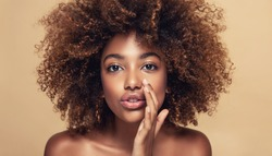 Beautiful african american woman with afro hair   telling a secret .Portrait  beauty  girl who is calling to someone .Funny  model  whispering about something. Expressive facial expressions