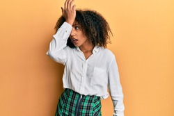 Beautiful african american woman with afro hair wearing scholar skirt surprised with hand on head for mistake, remember error. forgot, bad memory concept.