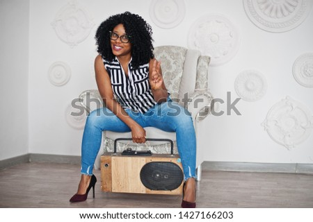 Beautiful african american woman with curly afro hair and eyeglasses posed in room with retro tape recording player.