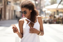 Beautiful african american woman with curly hair wearing fashionable sunglasses, holding smart phone in hand, walking on the italian street at sunny summer day.