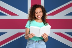 Beautiful African-American young girl reading book and flag of Great Britain as background. Learning English