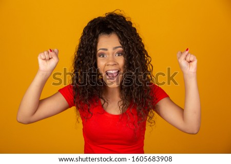 Beautiful African American young woman happy and excited celebrating victory expressing big success, power, energy and positive emotions. Celebrates new job joyful.