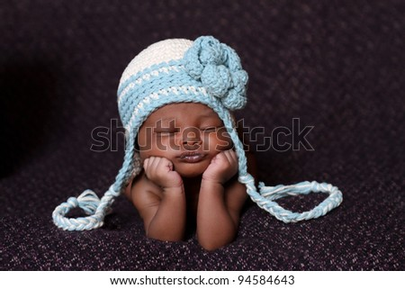 Beautiful African baby resting on her elbows and hands