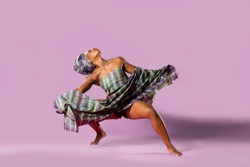 Beautiful African Black girl wearing traditional colorful African outfit does a dramatic aggressive crouching dance move against a colorful purple background