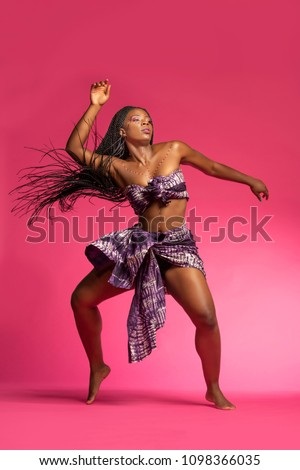Beautiful African Black girl wearing traditional colorful African outfit does a dramatic dance move against a colorful pink background