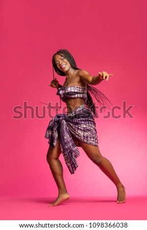 Beautiful African Black girl wearing traditional colorful African outfit does a dramatic dance move against a colorful pink background #1098366038
