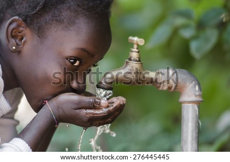 Beautiful African Child Drinking from a Tap (Water Scarcity Symbol).  Young African girl drinking clean water from a tap. Water pouring from a tap in the streets of the African city Bamako, Mali. #276445445