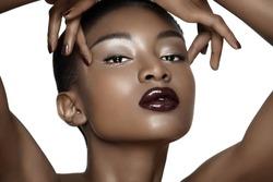Beautiful African fashion model closeup. Plum lipstick and dark nail polish. Posing over white background.