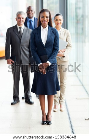 beautiful african female business leader with team standing on background
